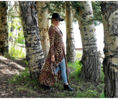 SheShe of the SheShe Show wearing a leopard wrap dress walking through  large aspen trees