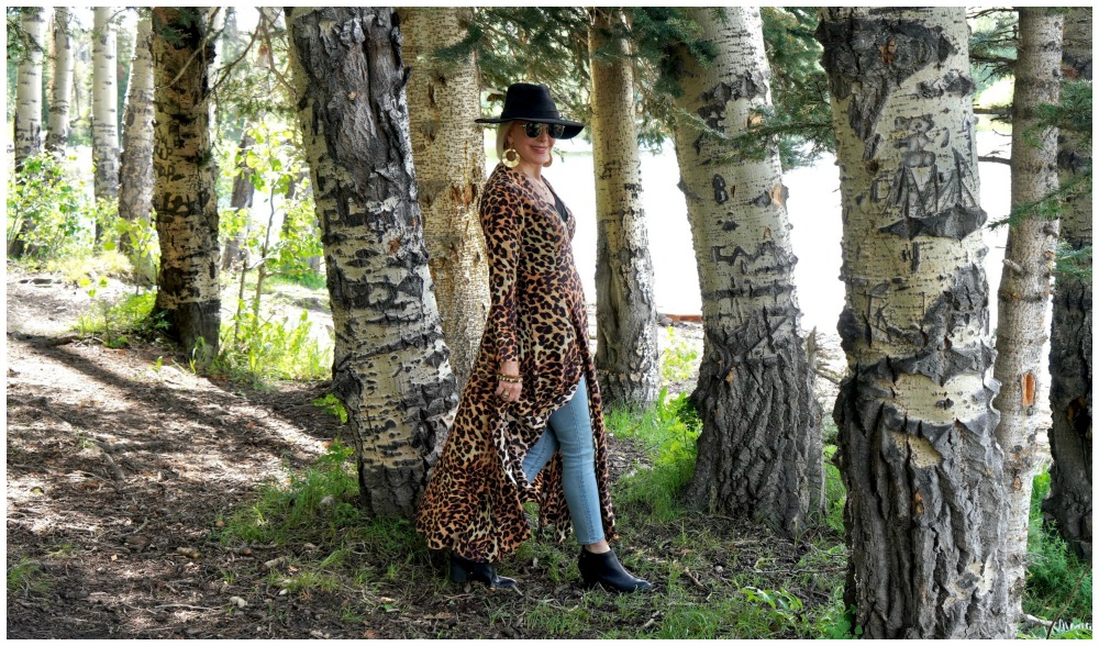 SheShe of the SheShe Show wearing a leopard wrap dress walking through  large aspen trees