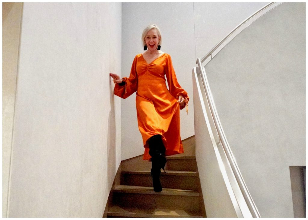 Sheree of the SheShe Show coming down stairs wearing orange satin dress