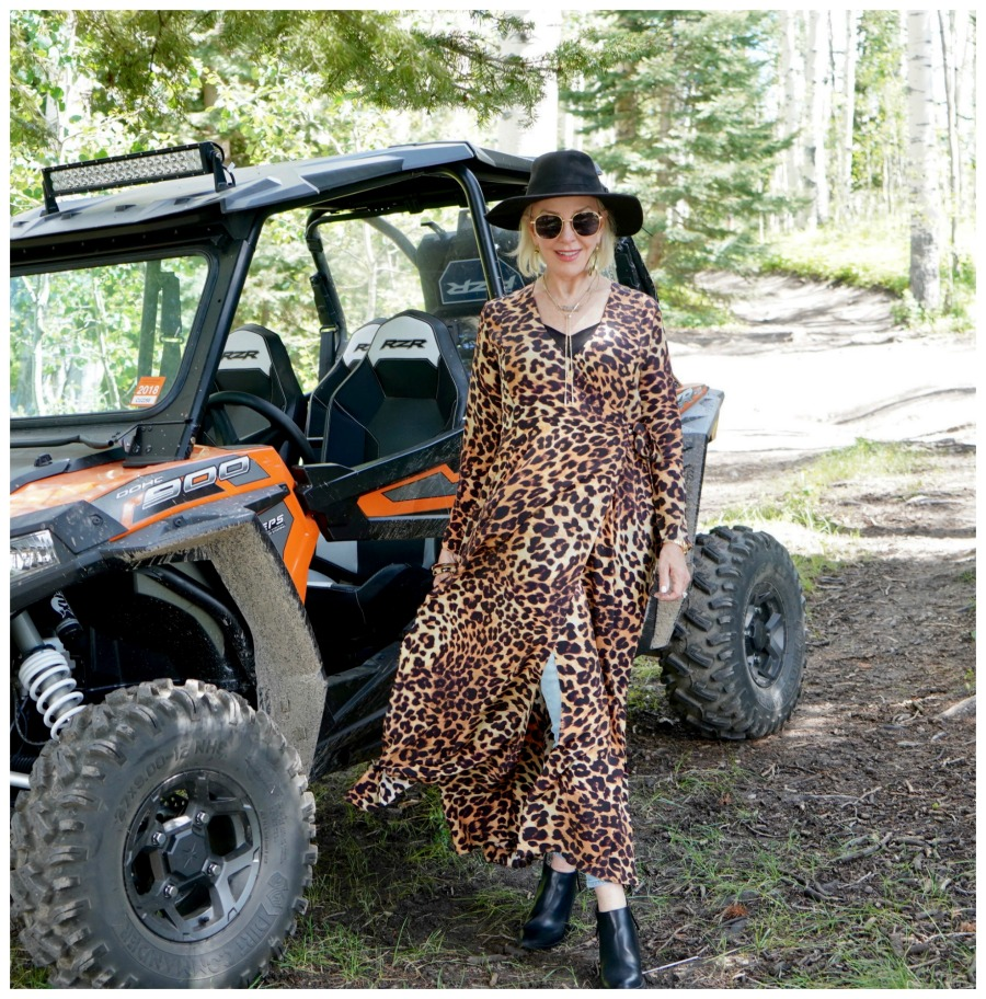 SheShe of the SheShe Show wearing a leopard wrap dress over hight blue jeans and black hat