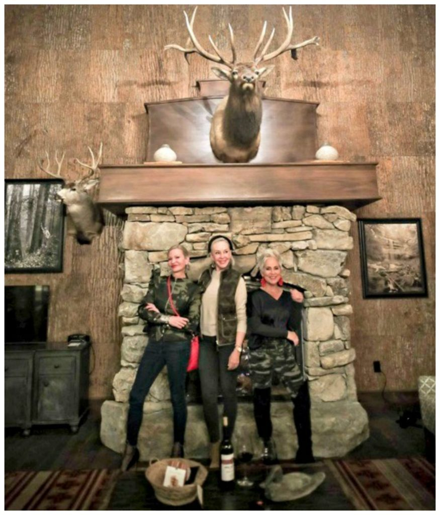 Jamie, SheShe & Shauna standing infront of stone fireplace at Cypress Lodge
