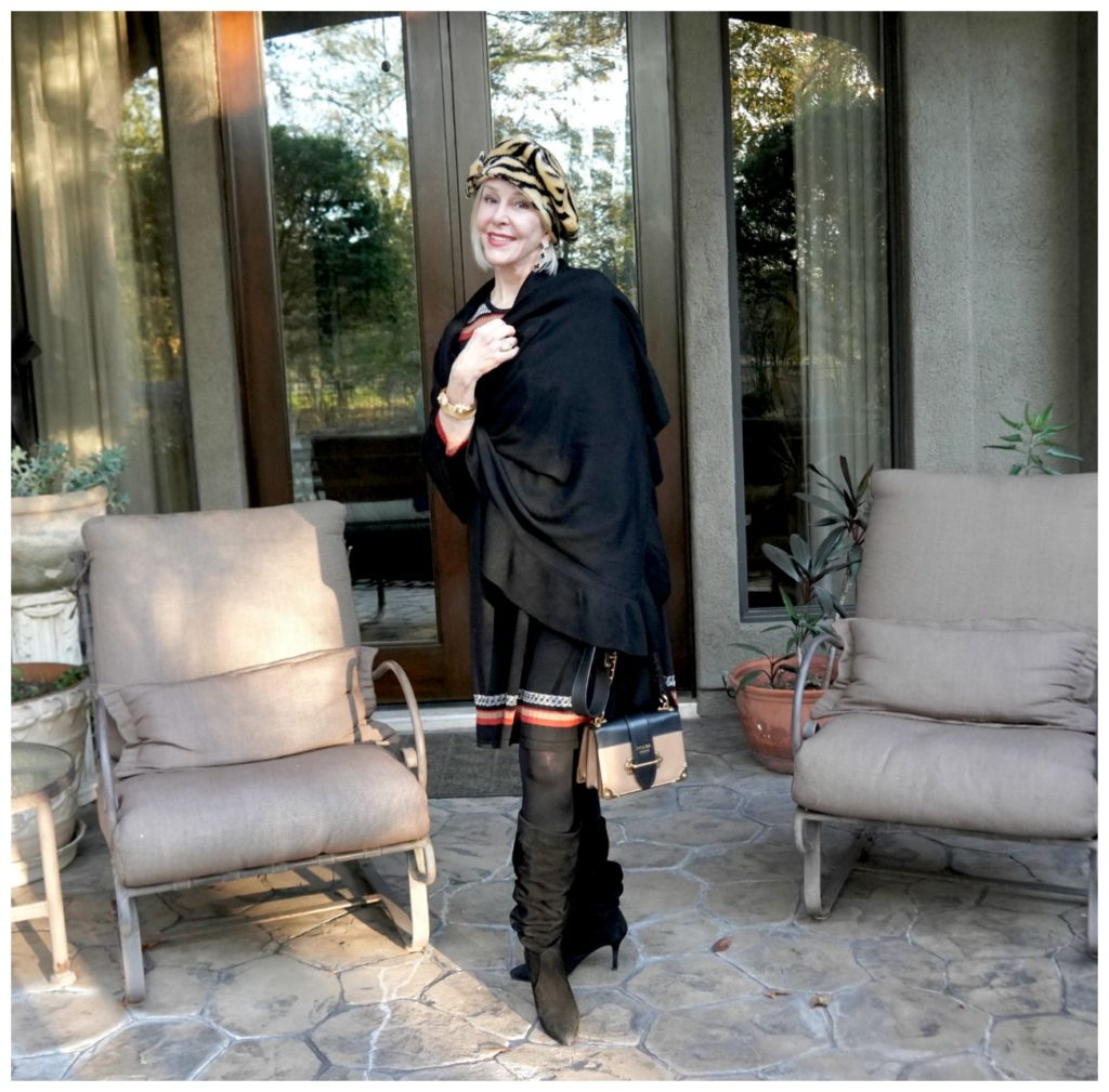 Sheree of the SheShe Show wearing a black wrap over a sweater dress and hat