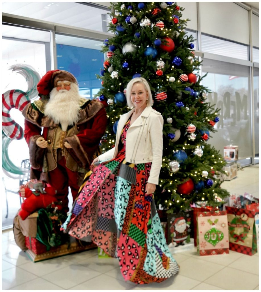 Sheree of the SheShe Show standing in front of Christmas tree wearing a patchwork print maxi dress