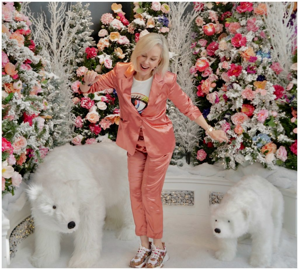 Sheree Frede of the SheSheShow weqring a satin 2 pc pant suit standing in a room of flowers and 2 stuffed polar bear animals