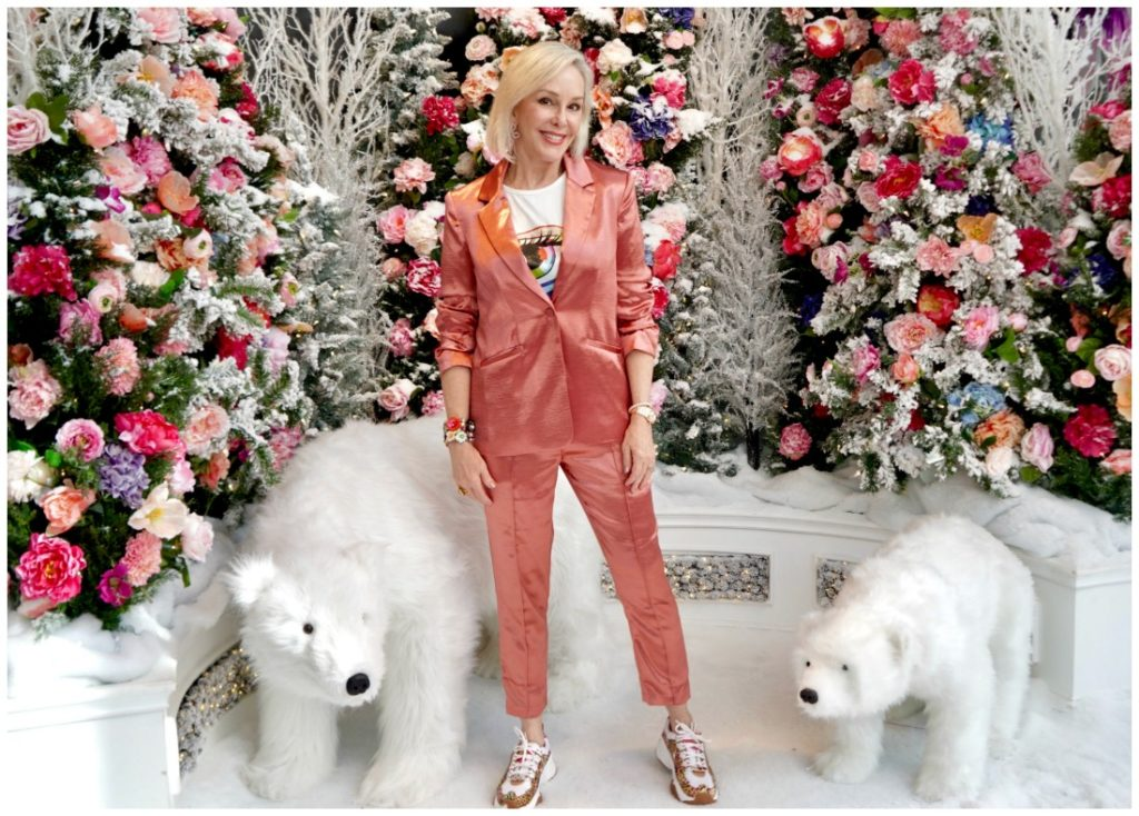 Sheree of the SheSheShow standing in front of pink and coral flowers and 2 stuffed polar bears