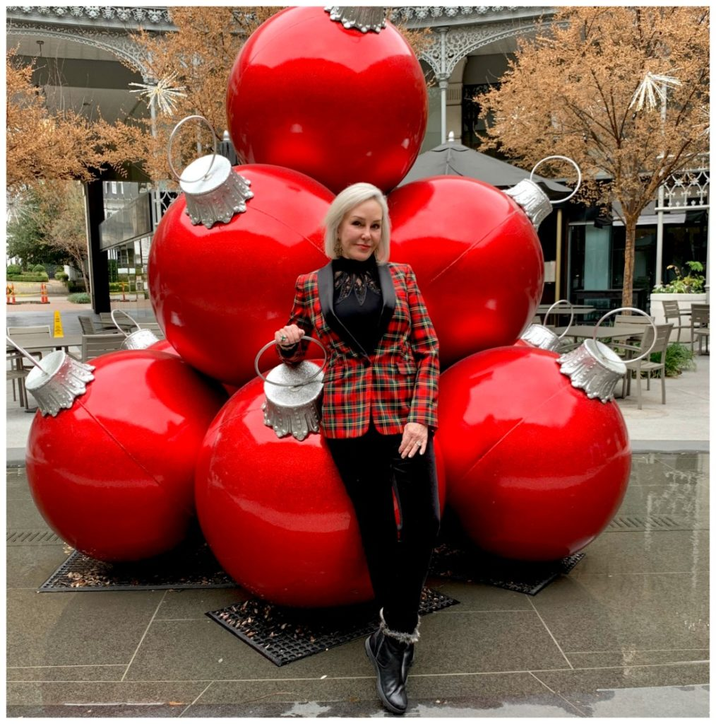 Sheree Frede of the SheSheSHow standing in front of large red outdoor ornaments wearing a red plaid jacket over black pants