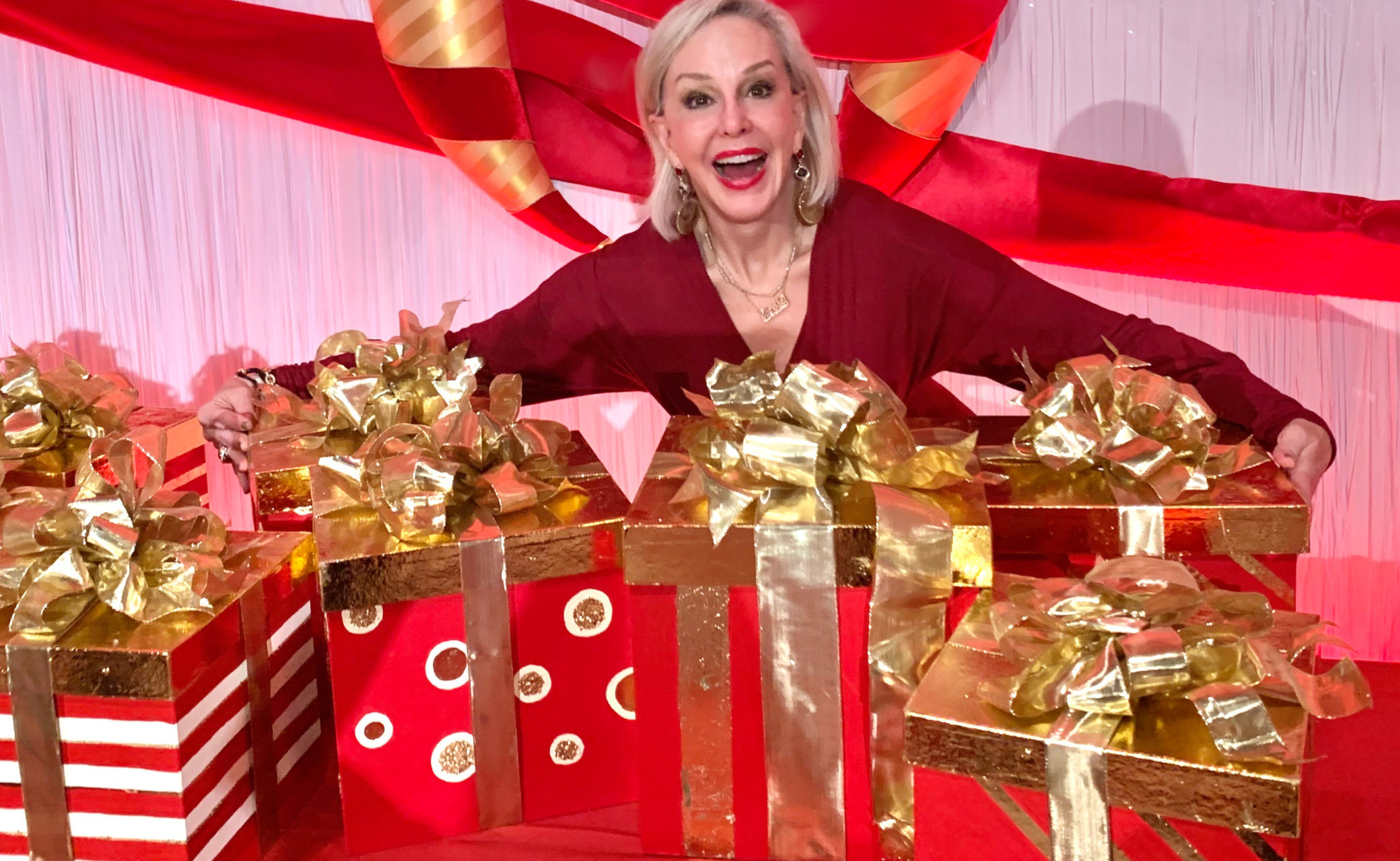 Sheree Frede of the SheShe Show standing behind a lot of wrapped Christmas presents