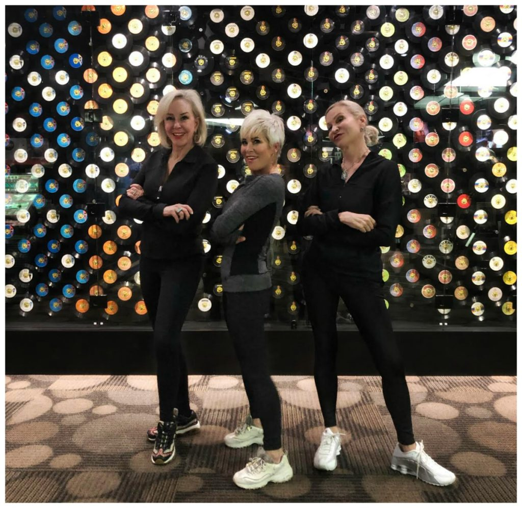 Sheree, Shauna & Jamie wearing black athleisure wear standing in front of a wall of 45 records