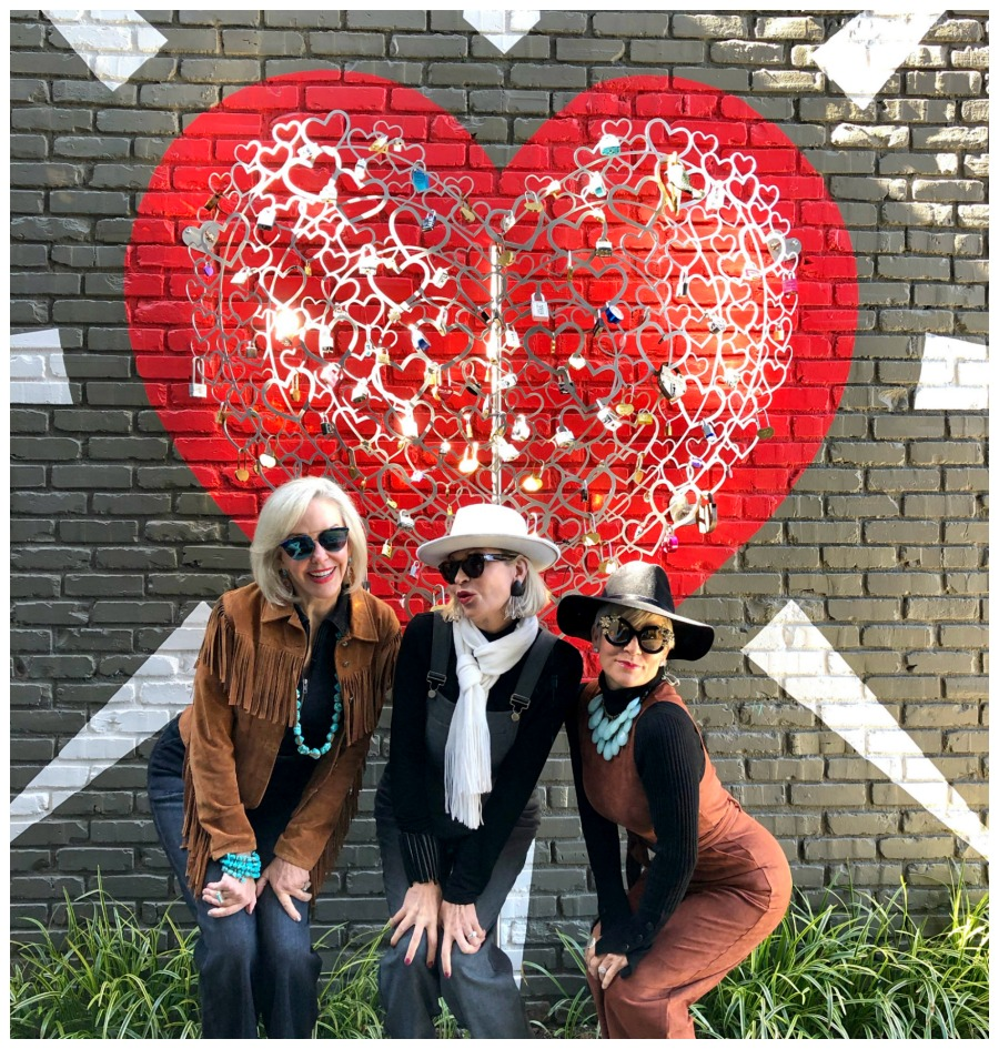 SheShe, Jamie, and Shauna posing in front of a heart wall mural