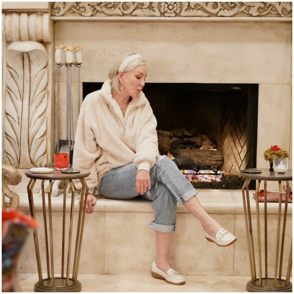 Sheree of the SheShe Show wearing a white sherpa pullover top, ripped jeans, and white loafers