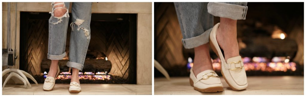 Legs wearing white loafers and jeans in front of a fireplac