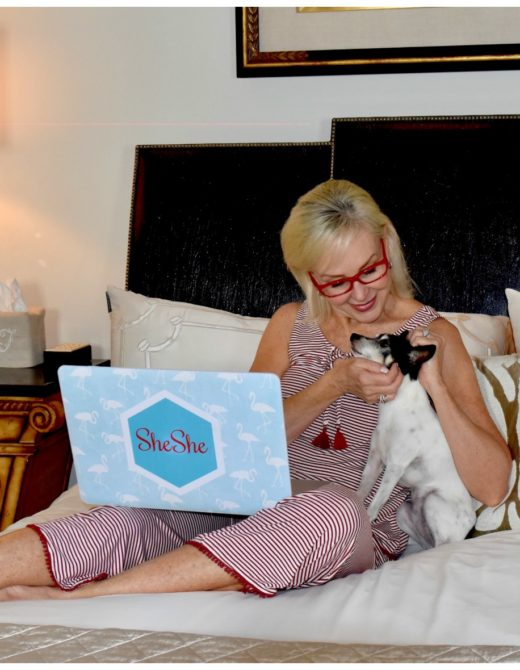 Sheree Frede of the SheShe Show on bed with her Toy Fox Terrier dog Pippa