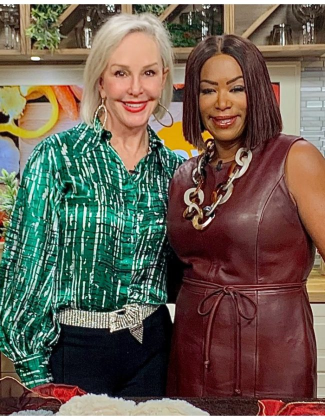Sheree of the SheShe Show wearing green to with hostess Debra Duncan wearing burgundy leather dress
