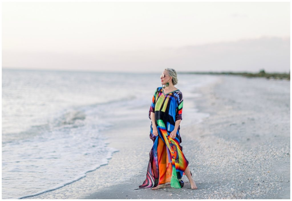 Sheree of the SheShe Show on the beach wearing an abstract multi colored kaftan