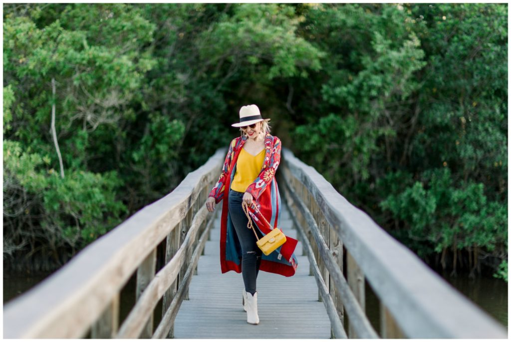 Sheree of the SheSheShow walking on wood walking bridge wearing a red print duster over  blue jeans and yellow camisole. Panama hat