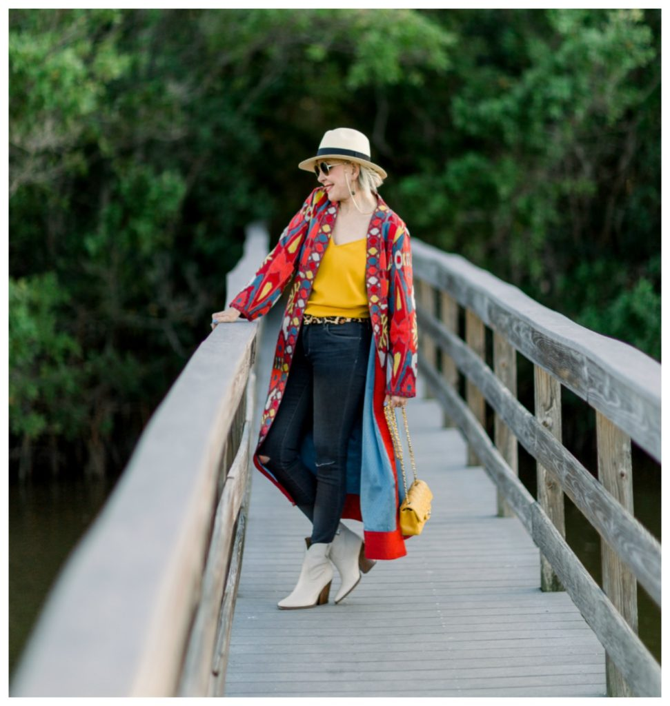 Sheree Frede of the SheShe Show on wooden bridge wearing jeans and a duster