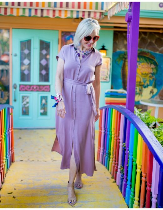 Sheree Frede of the SheSheShow walking across a bridge with rainbow railing wearing a lilac dress by Chicos