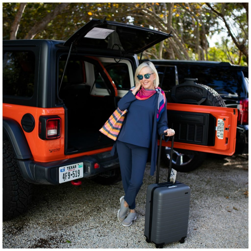 Sheree of the SheShe SHow loading suitcase and tote bag wearing Nic + Zoë Tech Stretch pants tank and jacket