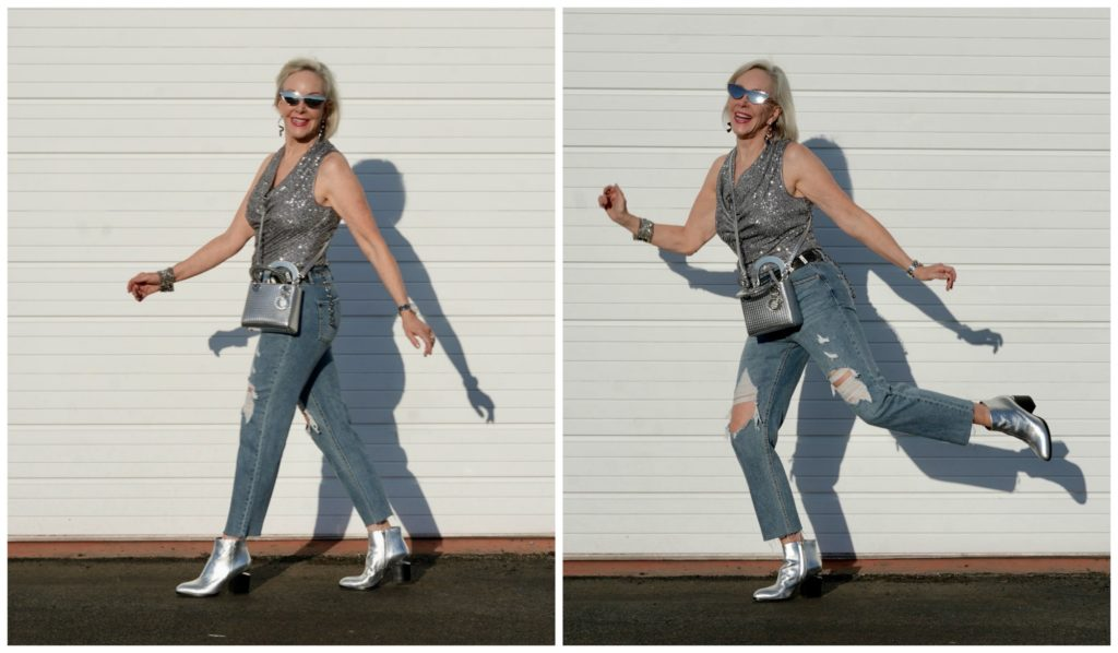 Sheree Frede of the SheShe Show walking in front of a white wall wearing gray sequin cowl neck top by Eliza J with ripped denim jean and silver booties