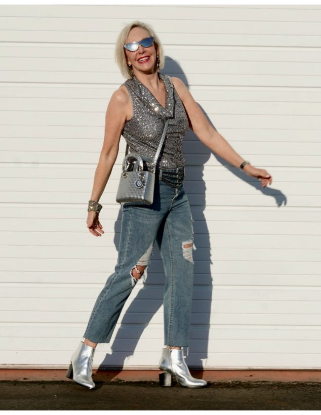 Sheree Frede of the SheShe Show standing in front of a white wall wearing gray sequin cowl neck top by Eliza J with ripped denim jean and silver booties
