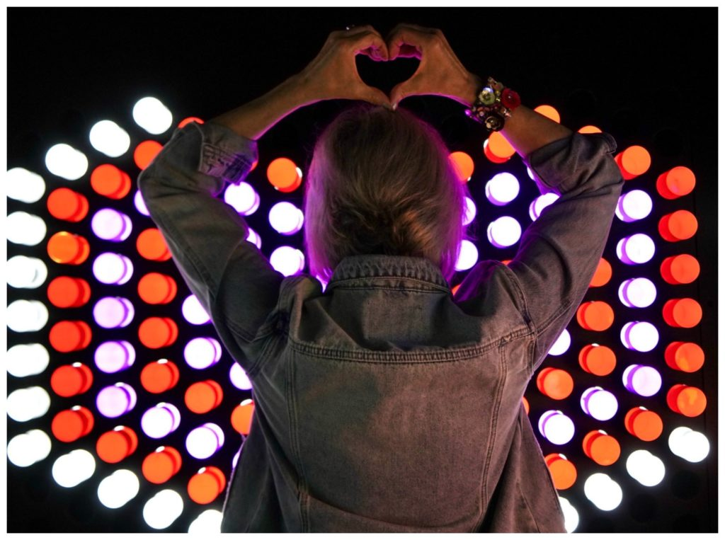 Night lights behind Sheree Frede's back. Heart sign with hand over head