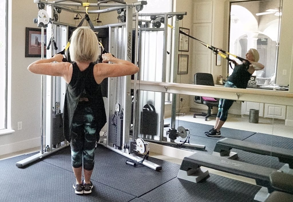 Sheree Frede of the SheShe Show using her trx straps in her workout room and wearing workout apparal