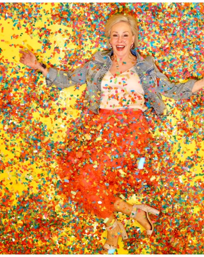Sheree Frede of the SheShe Show wearing a bright coral midi length skirt, denim jacket over white camisole and rhinestone shoes laying on the floor covered in colorful confetti