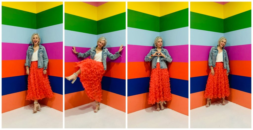 Sheree Frede of the SheShe Show wearing a bright coral midi length skirt, denim jacket over white camisole and rhinestone shoes