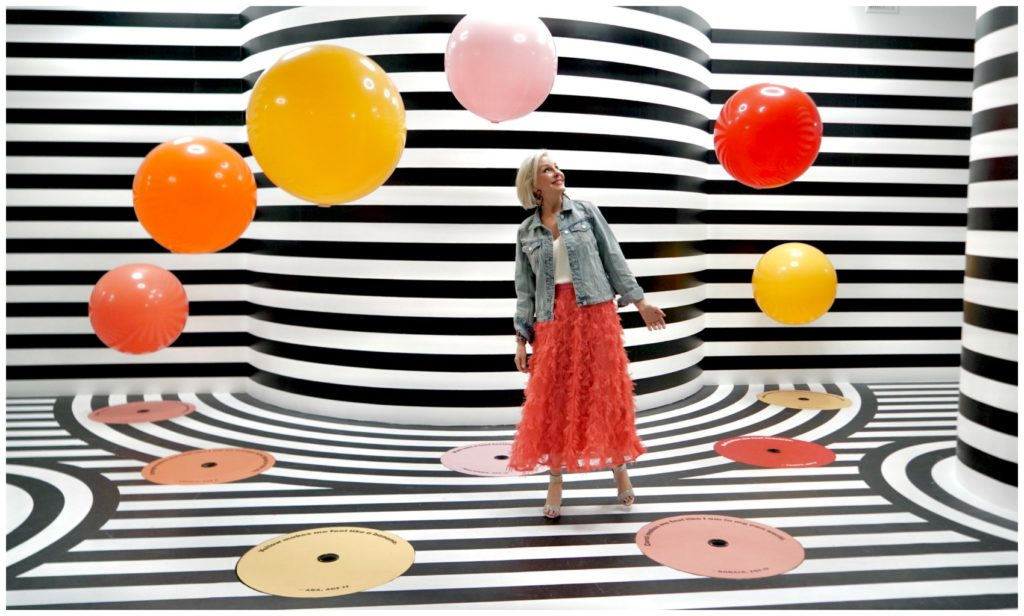 Sheree Frede of the SheShe Show wearing a bright coral midi length skirt, denim jacket over white camisole and rhinestone shoes staniding in a black and white strips room with large balloons floating around