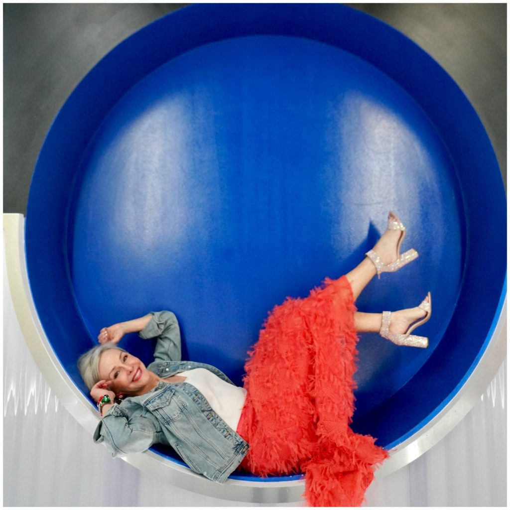 Sheree Frede of the SheShe Show wearing a bright coral midi length skirt, denim jacket over white camisole and rhinestone shoes laying on her back inside a large circle with blue background