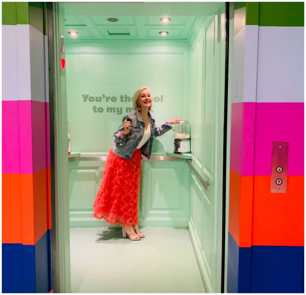 Sheree Frede of the SheShe Show wearing a bright coral midi length skirt, denim jacket over white camisole and rhinestone shoes standing inside a fun elevator
