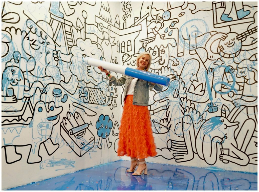 Sheree Frede of the SheShe Show wearing a bright coral midi length skirt, denim jacket over white camisole and rhinestone shoes standing in a drawing room holding a giant marker