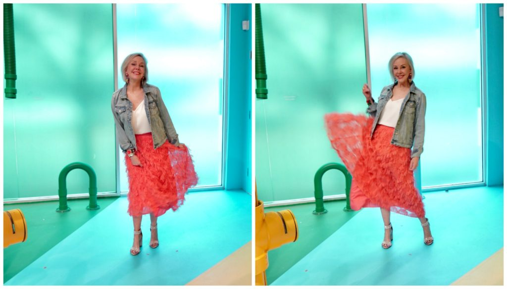 Sheree Frede of the SheShe Show wearing a bright coral midi length skirt, denim jacket over white camisole and rhinestone shoes swishing her skirt