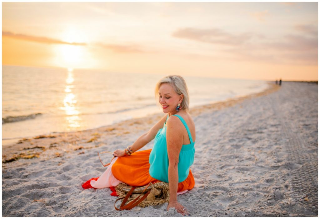 Sheree Frede of the SheShe Show on the beach at sunset wearing a orange and turquoise maxi dress