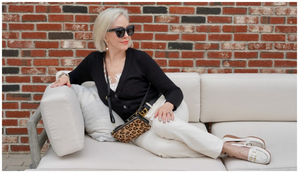 Sheree Frede of the SheShe Show sitting on a big offwhite sofa wearing off white jeans and black sweater.