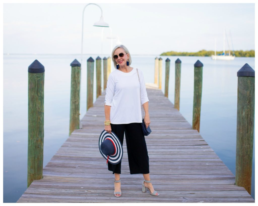 Sheree Frede of the SheSheShow standing on a pier wearing split skirt with white tunic top