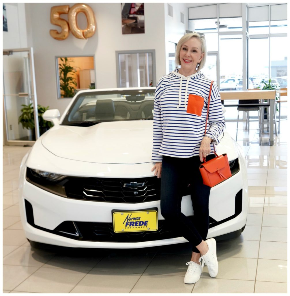 Sheree Frede standing in front of white Chevrolet wearing a white and blue stripe with orange pocket