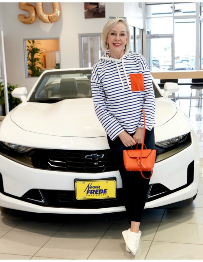 Sheree Frede standing in front of white Chevrolet wearing white and blue stripes with orange pocket