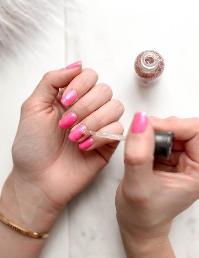 painting nails with pink polish