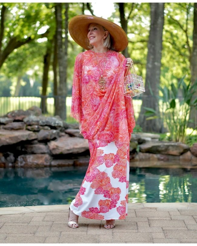 Sheree Frede of the SheShe Show by swimming pool wearing a coral floral kaftan