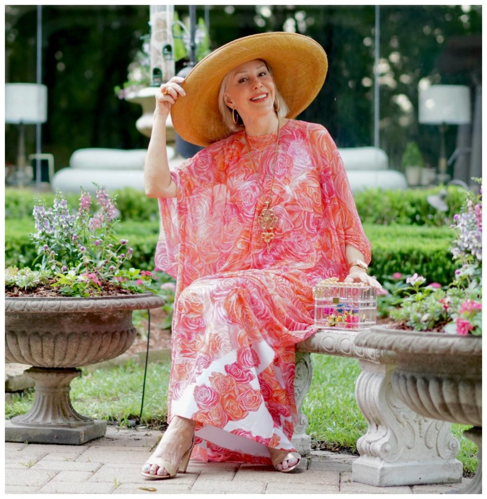 Sheree Frede of the SheShe Show sitting by on a bench wearing a coral floral kaftan