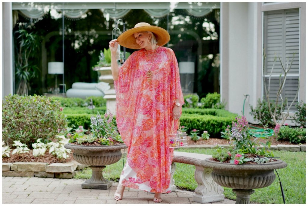 Sheree Frede of the SheShe Show standing by on a bench wearing a coral floral kaftan