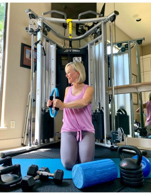 Sheree Frede of the SheShe Show in home gym wearing a pink tank over gray leggings