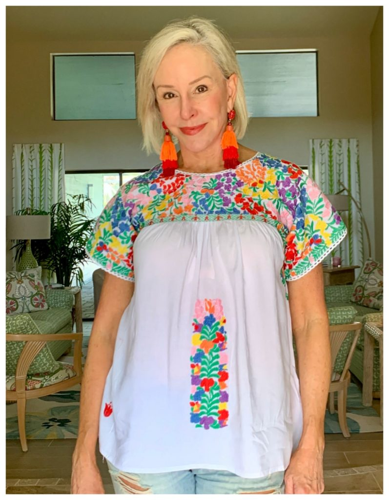 Sheree Frede of the SheShe Show wearing white floral embroidered top over denim shorts