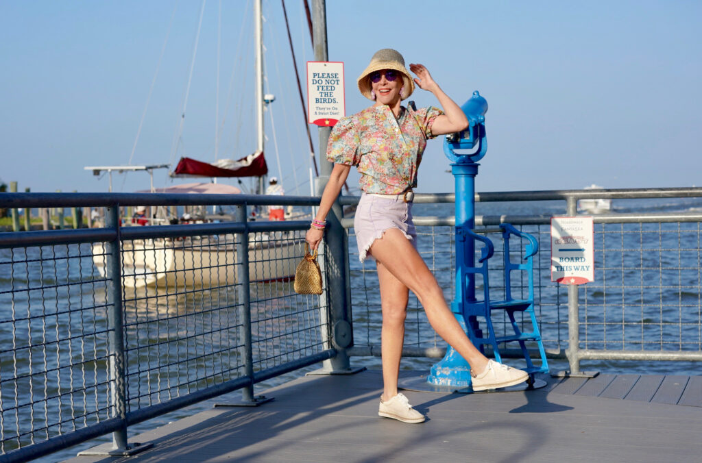 Sheree Frede of the SheShe show standing on pier by the water wearint laender shorts and floral puffed sleeve top and straw bucket hat