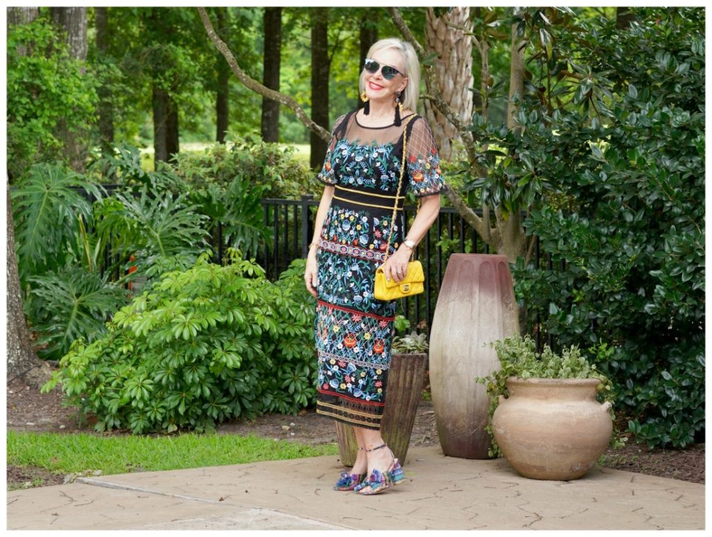 Sheree Frede of the SheShe Show standing by swimming pool wearing sunglasses and a black floral dress