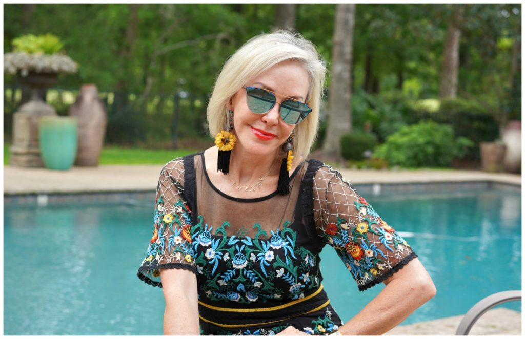 Sheree Frede of the SheShe Show sitting by swimming pool wearing sunglasses and a black floral dress