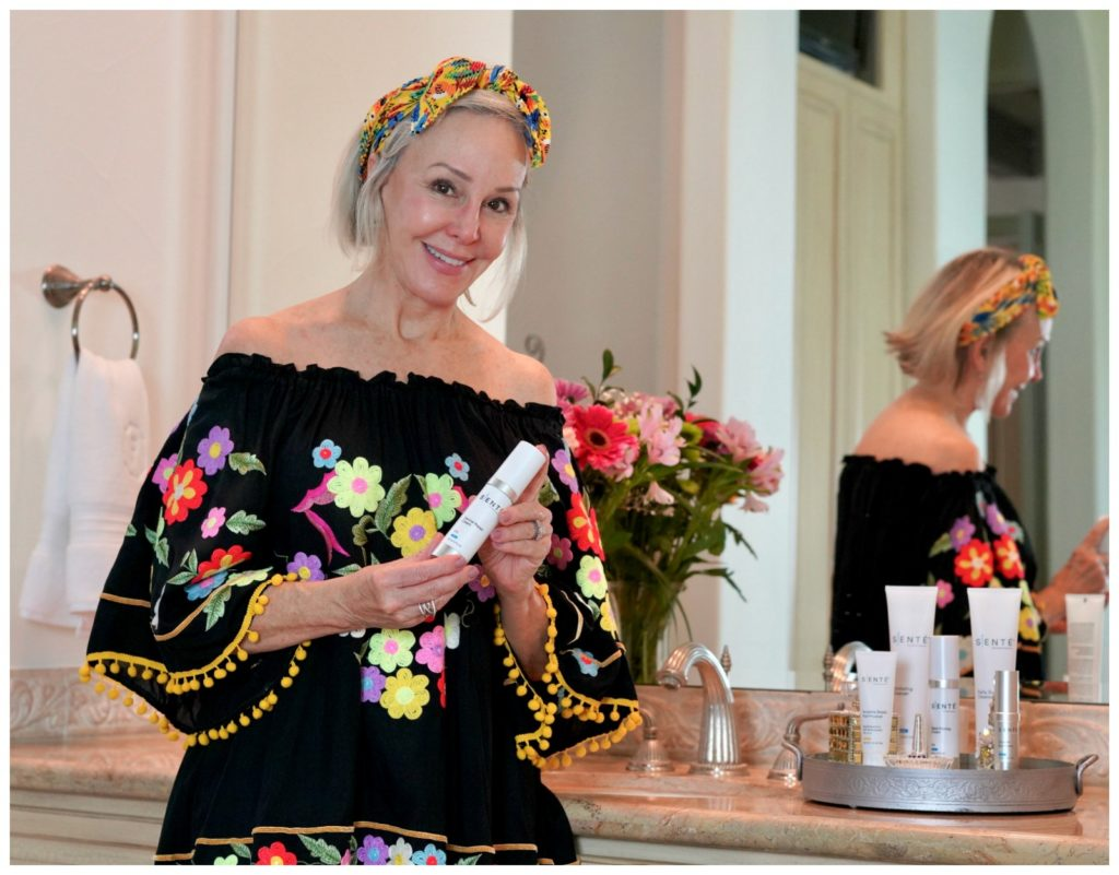 Sheree Frede founder of the SheSheShow applying Sente skincare in her bathroom wearing a black floral offtheshoulder top