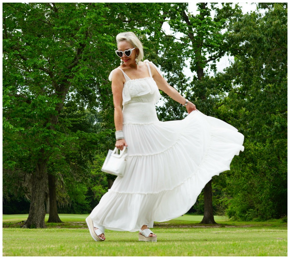 Sheree Frede of the SheShe Show wearing a white flowy maxi dress on a green lawn and wooded background