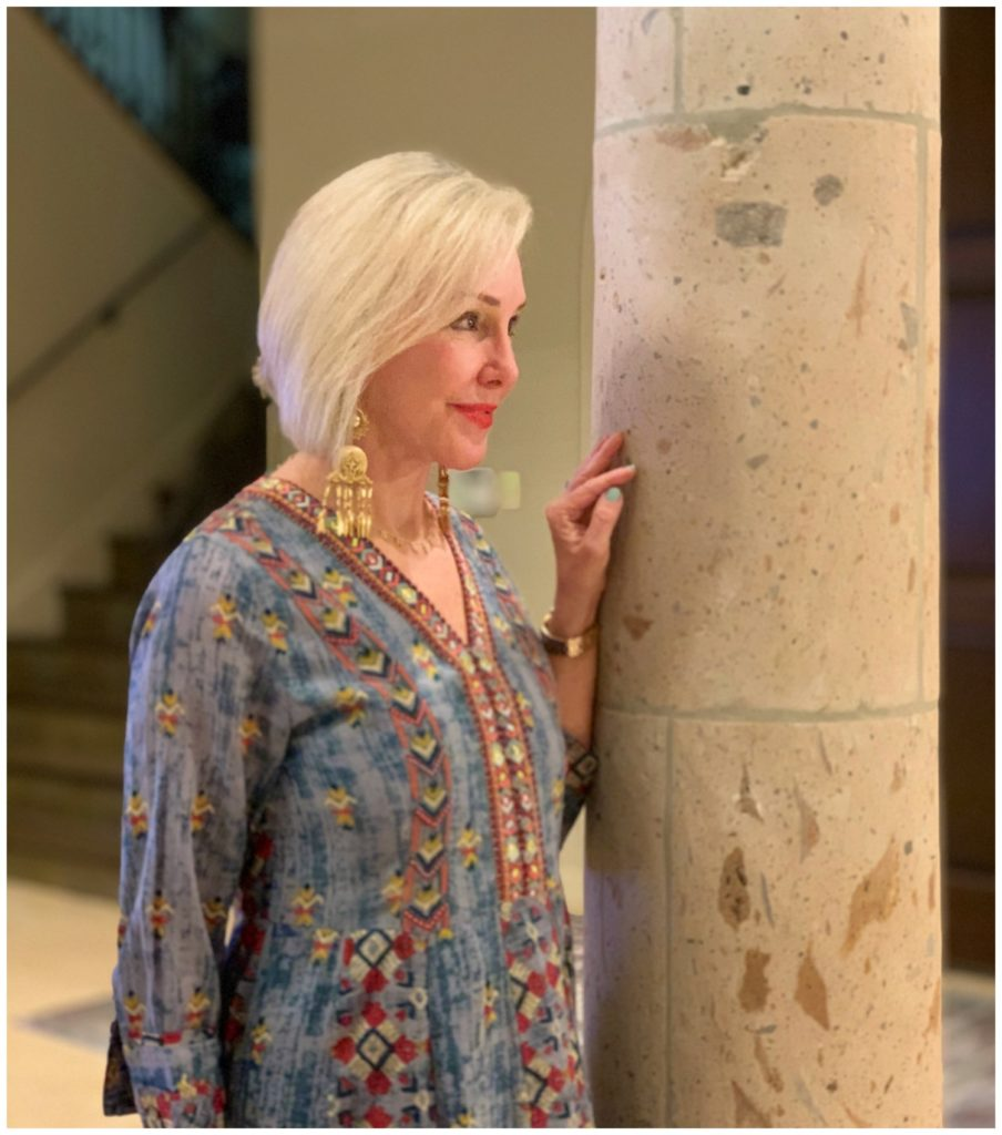 Sheree Frede of the SheShe Show standing in foyer by column wearing a chambray maxi dress accented in embellishments